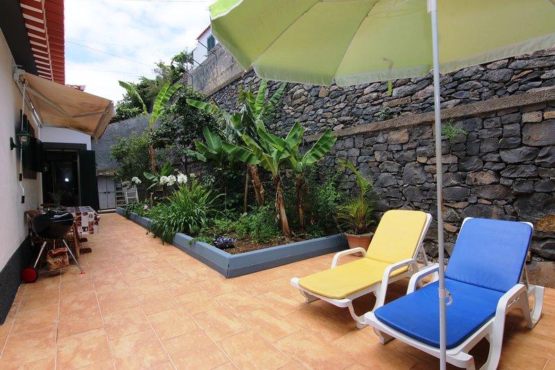 Ruime patio met ligbedden, parasol en barbecue
