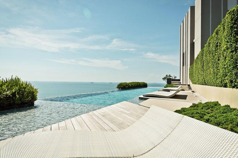 Tumbona en la piscina con vista al mar