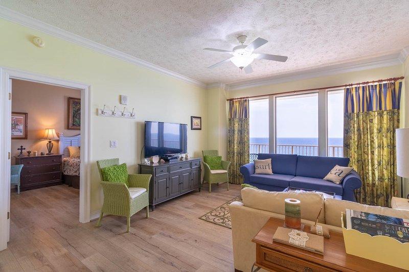 Salon tropical bleu et vert clair avec télévision grand écran plat et canapé-lit queen