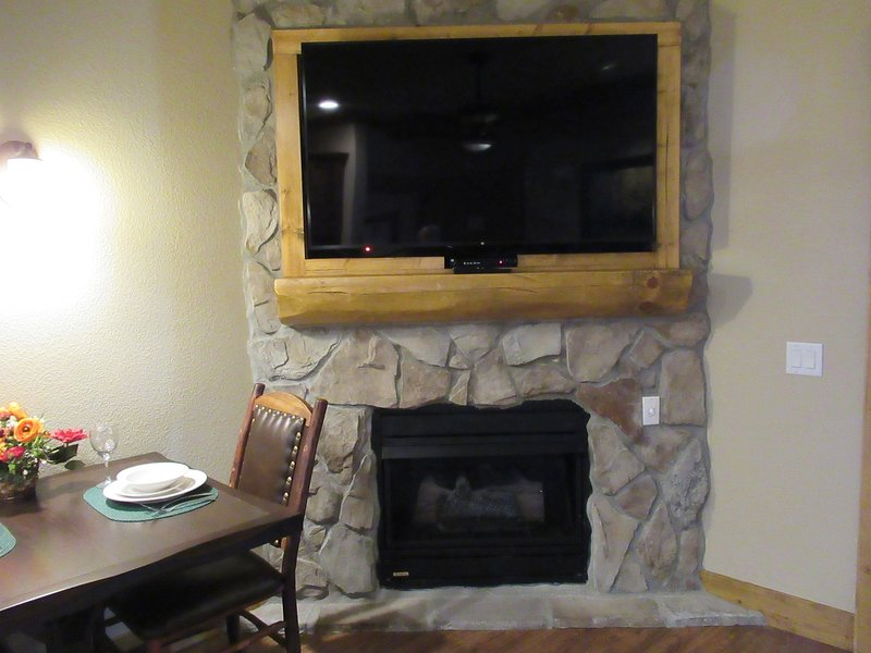 Gas log fireplace with retractable tv