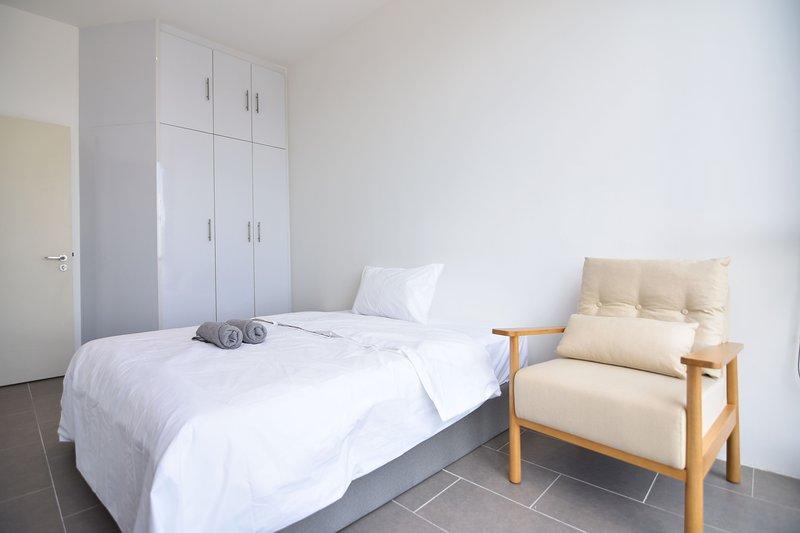 El dormitorio principal con una cama de matrimonio y almohadas de felpa.
