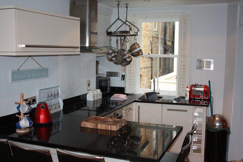 Cuisine de cuisine moderne avec plaques à induction et four, micro-ondes, lave-vaisselle et réfrigérateur.