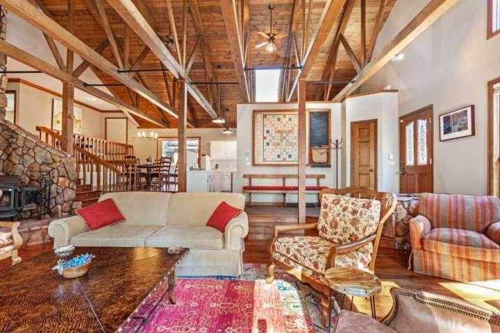 Weitläufige Familie / Wohnzimmer mit Holzofen, Smart-TV und Holzbalkendecken.