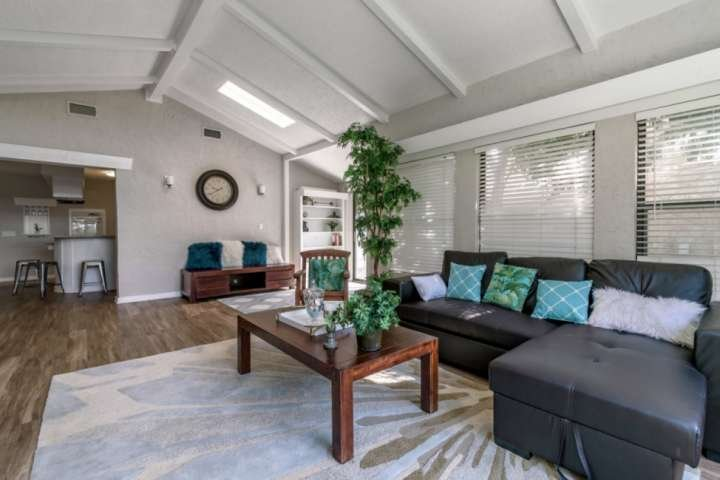Living room opens to kitchen and dining and has sliding door that walks out to outdoor seating.