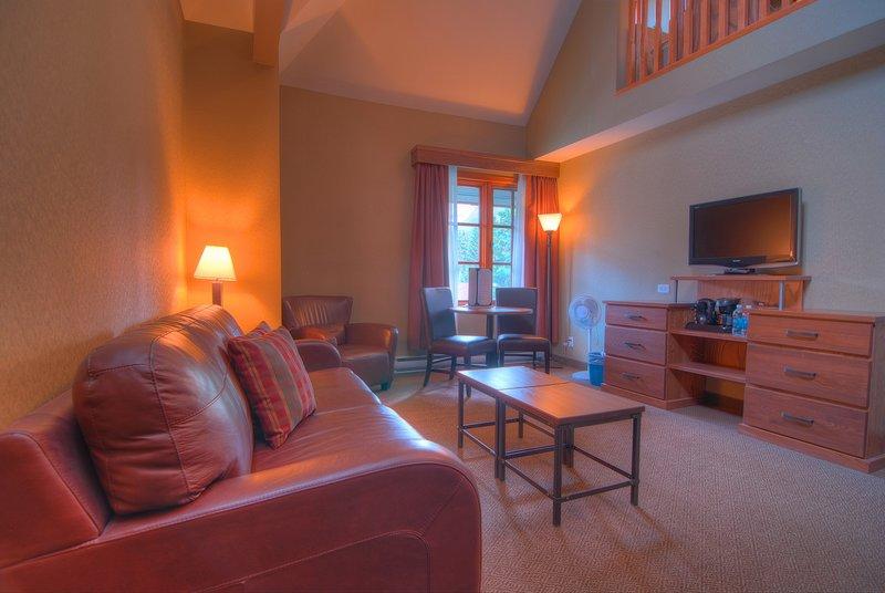 Regrese a esta impresionante sala de estar con televisor de pantalla plana y disfrute de una copa de vino.