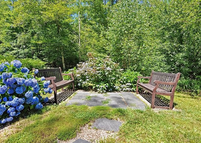 Garden sitting area with benches among the hydrangeas.