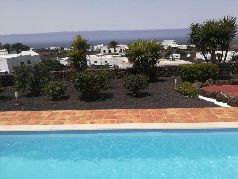 Piscina, giardino in pietra arenaria nera e vista sul mare