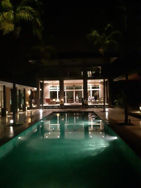 Vista nocturna de la casa y la piscina