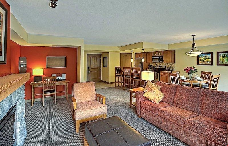 Esta amplia sala de estar cuenta con una acogedora chimenea, un televisor de pantalla plana y un reproductor de DVD.