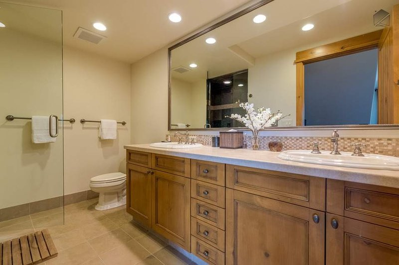 The Master Bathroom features rich wood cabinets, a large double vanity, and a walk-in shower.