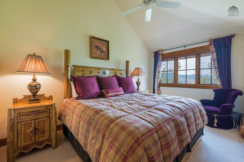 The Master Bedroom on the second floor has cozy sloped ceilings and large windows to let in natural light.