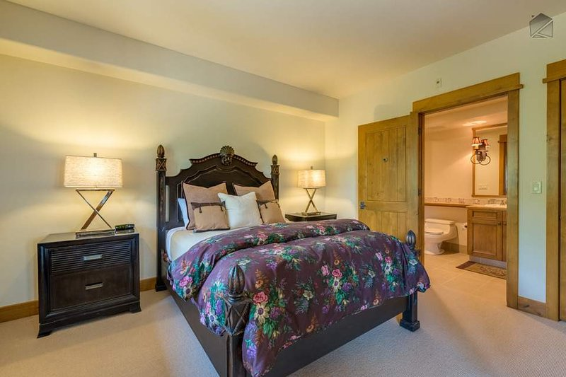 The second guest bedroom on the first floor has a queen-size bed and attached bathroom.