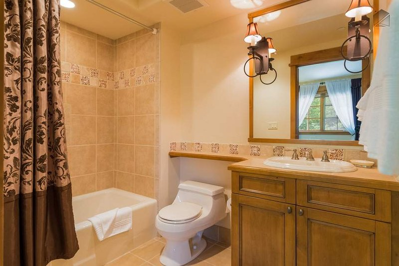 The guest ensuite bathroom has a single sink and a shower/tub combination.