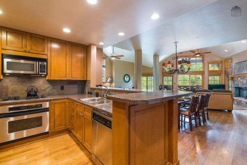 Stainless steel appliances fill the kitchen, including an oven, 4-burner gas stove, microwave, and dishwasher.