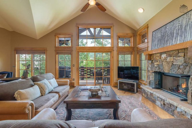 The living room has a traditional stone fireplace, a TV, and plenty of cozy seating.