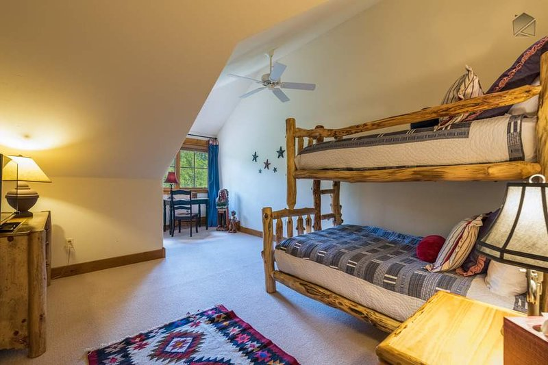 The well-designed bunk bedroom has a Captain's bunk setup with a twin over a full.