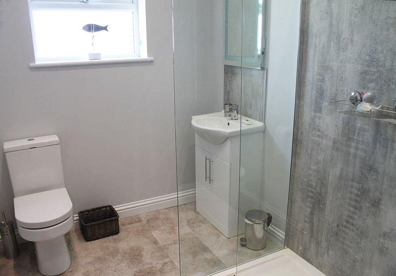 Moderno baño de estilo hotel con ducha a ras de suelo.