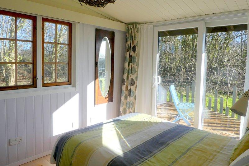 La chambre principale a des portes coulissantes à une véranda privée.