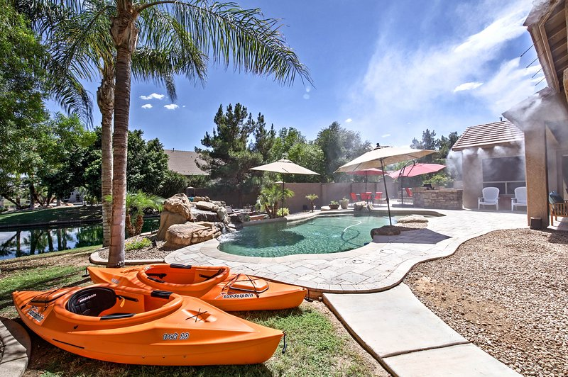 This backyard oasis includes a pool, hot tub, outdoor kitchen, and more!