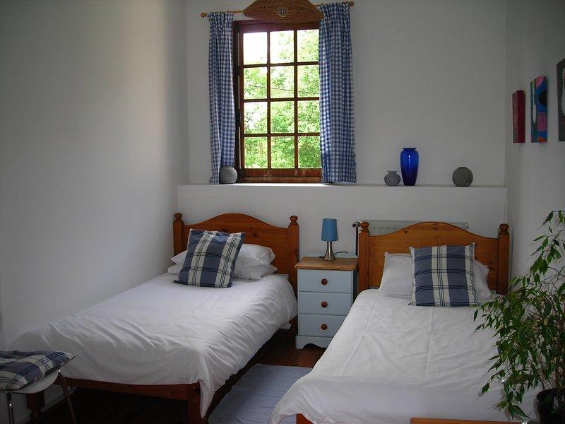 Chambre à deux lits au premier étage avec salle de douche attenante.