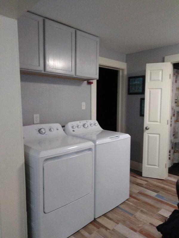 Lavadora y secadora con un gabinete con suministros de lavado y limpieza. Se mantuvo alejado de los niños.