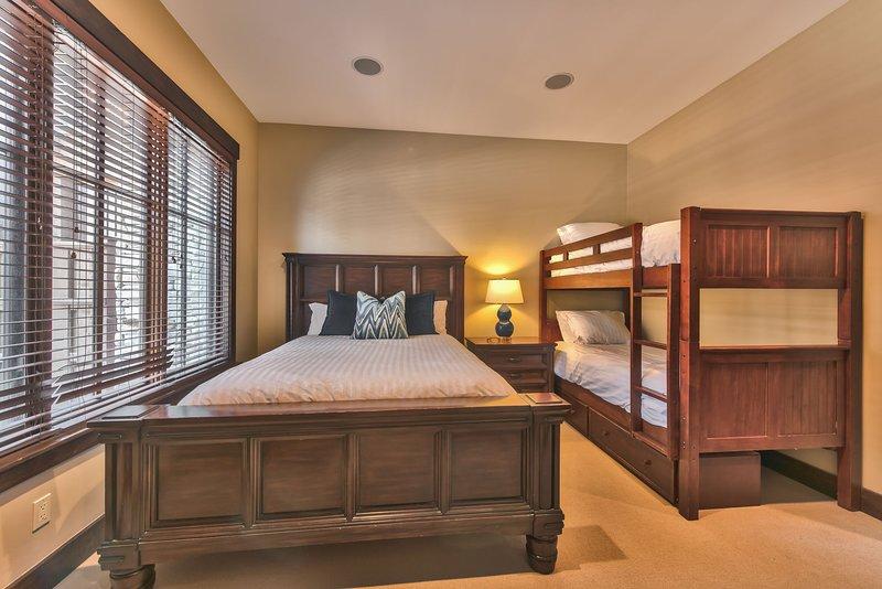 Camera da letto di livello inferiore 2 con un letto matrimoniale, una doppia più letti a castello, TV e bagno privato completo