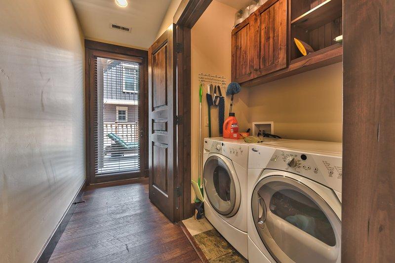 Corridoio inferiore con ingresso dal garage, armadio con lavatrice / asciugatrice full size e accesso al patio posteriore