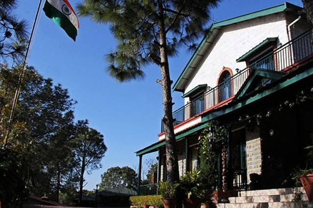 Fachada de esta casa de vacaciones en Kasauli con nítidos cielos azules de montaña con pinos
