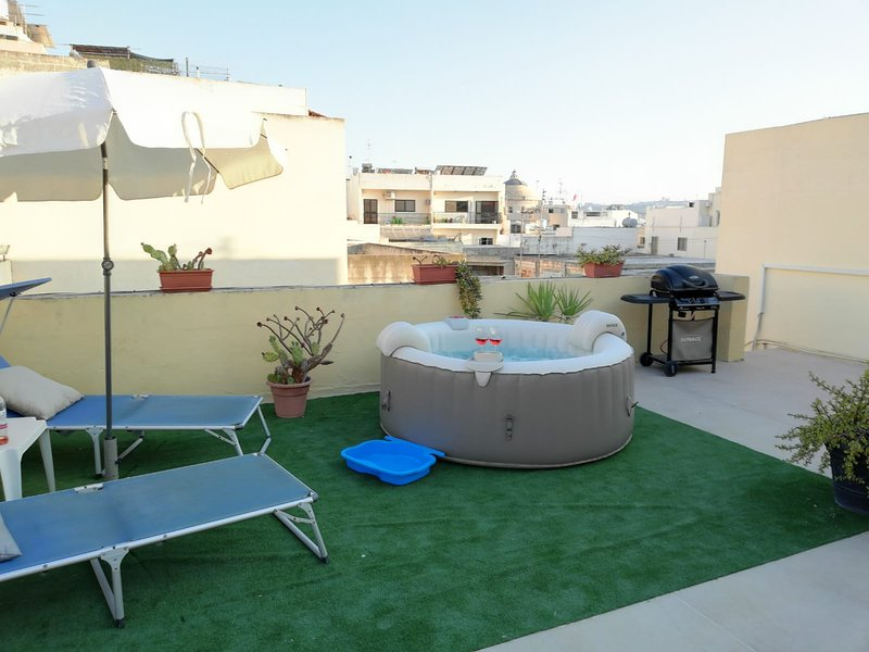 Private terrace with Mosta dome views, a Jacuzzi where to relax or sip a glass of wine.