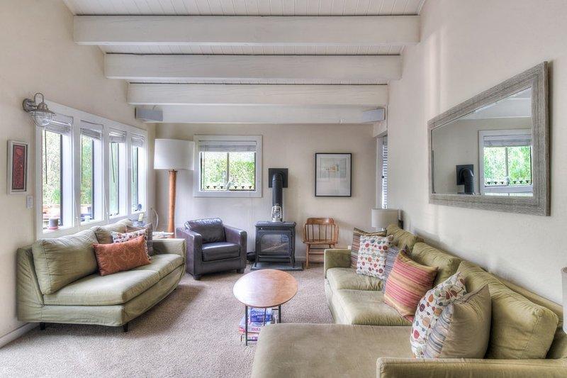Piano principale soggiorno con due divani, una sedia e camino
