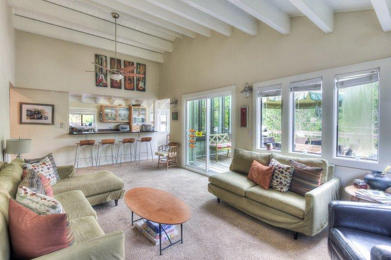 Sala de estar do piso principal com sofás, cadeiras, balcão da cozinha e deck ao ar livre
