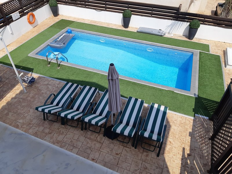 Large pool area with private pool sunbeds and gazebo.