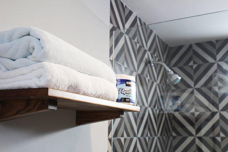 Amplio baño con comodidades como champú, agua caliente, toallas de baño y playa, papel higiénico