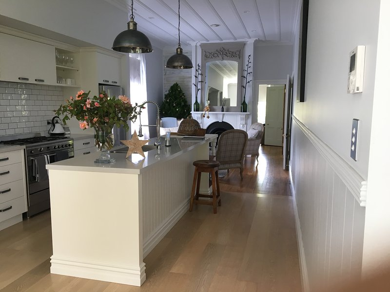 Cuisine ouverte avec vue sur le salon et accès au salon privé.