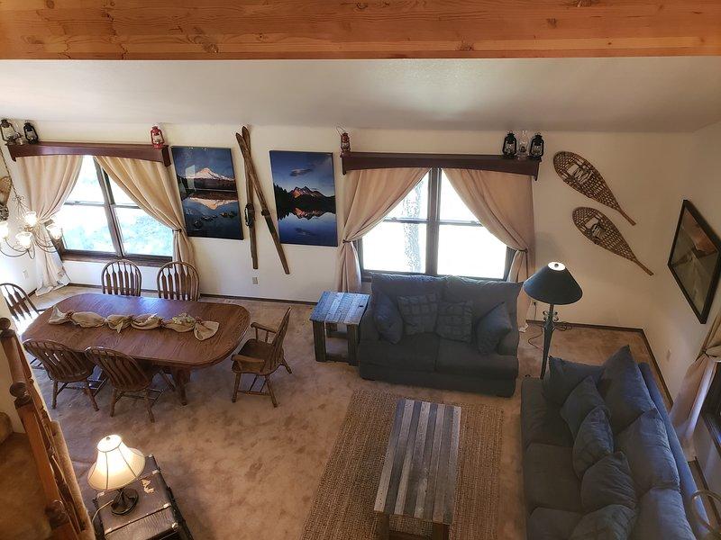 Sala de estar y comedor de nivel principal, espaciosa y profesionalmente decorada con vistas de 180 grados al bosque.