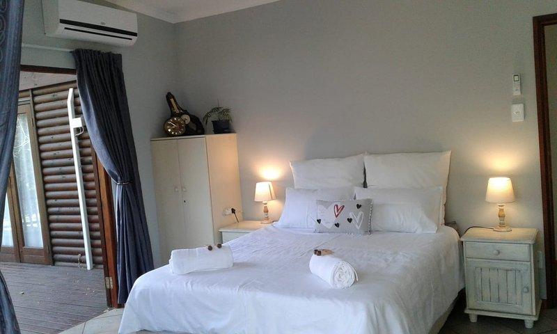 Dormitorio principal con cama queen size, ventilador de techo y aire acondicionado.