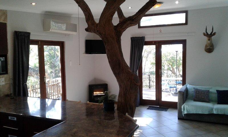 Sala de estar caminando hacia la cubierta con DSTV completo, aire acondicionado y chimenea.