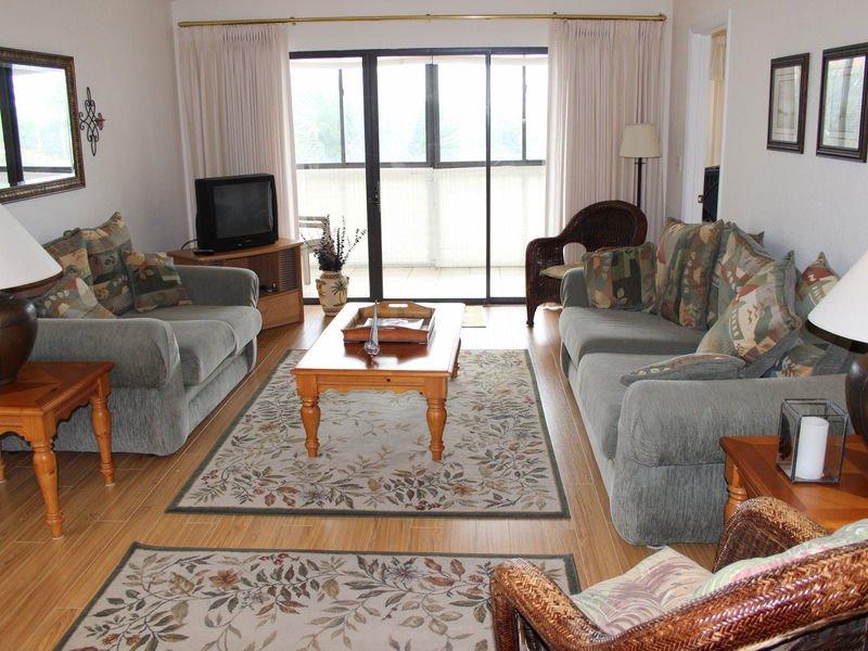 Sala de estar confortablemente amueblada con TV y barra deslizadora hacia el patio.