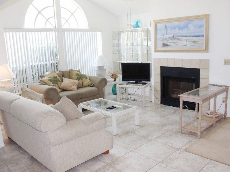 Sala de estar con TV de pantalla plana, DVD, chimenea y sofá cama.