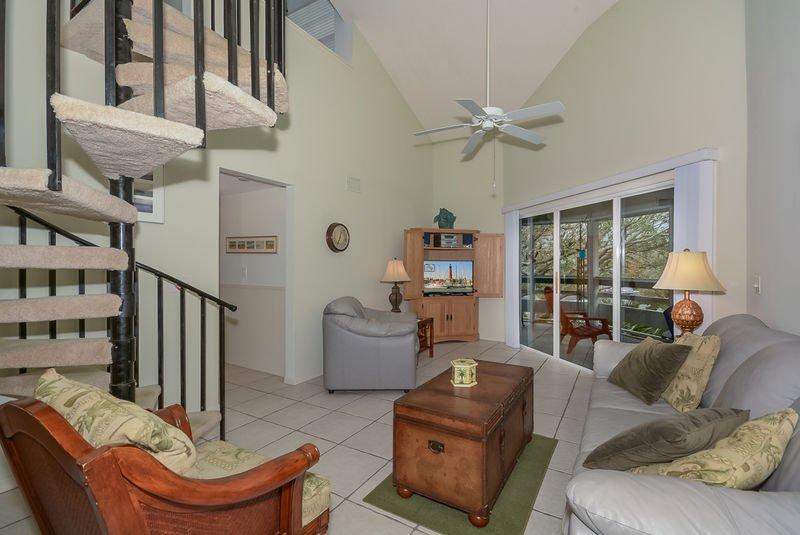 Los controles deslizantes conducen a la malla en el porche. La sala de estar tiene un televisor de pantalla plana. y DVD
