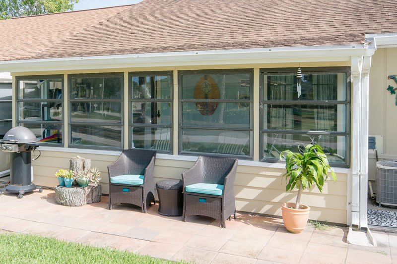 Enclosed back porch and outdoor grill.