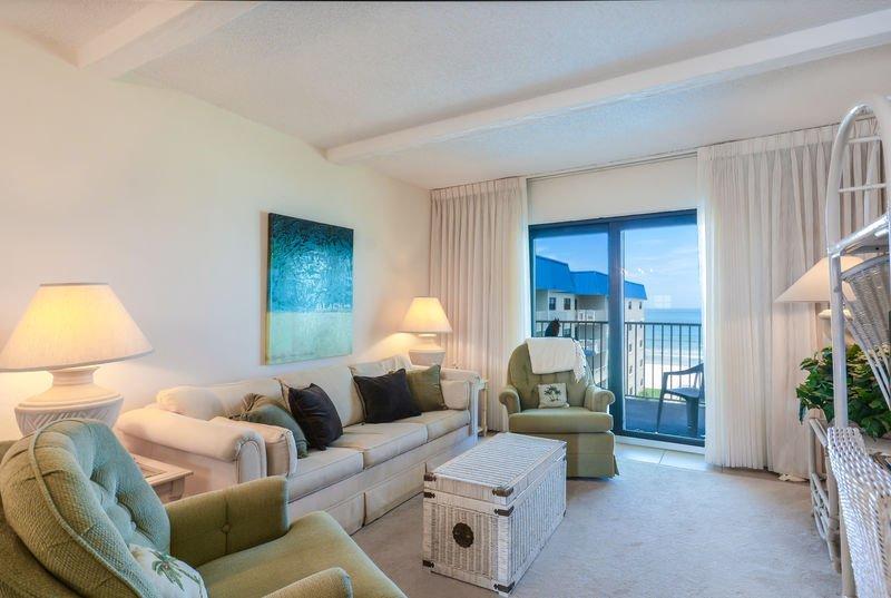Sala de estar com vista para o mar, TV e videocassete.