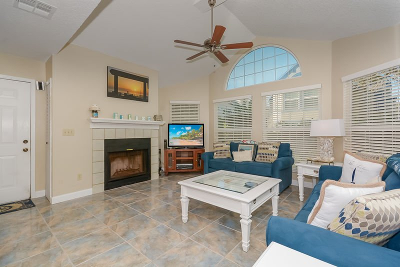 Spacious living room with vaulted ceilings, large flat screen TV, DVD, VCR, sofa sleeper and fireplace.
