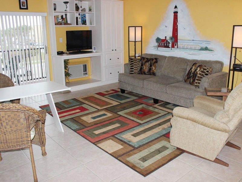 Zona giorno arredata confortevolmente con divano, poltrona reclinabile, TV a schermo piatto e lettore DVD.
