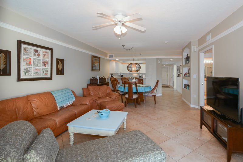 Large living area with plenty of room for entertaining or relaxing. Leather couches, flat screen TV and tiled floor.