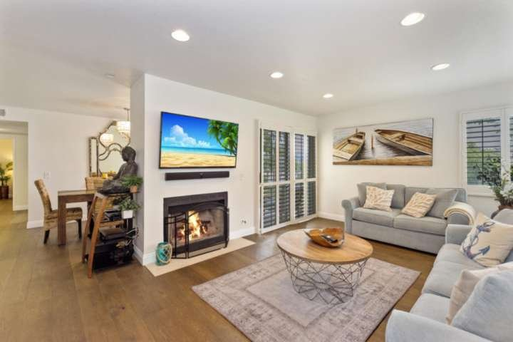 Enter into a spacious living room with beauiful wood floors and a sleeper sofa