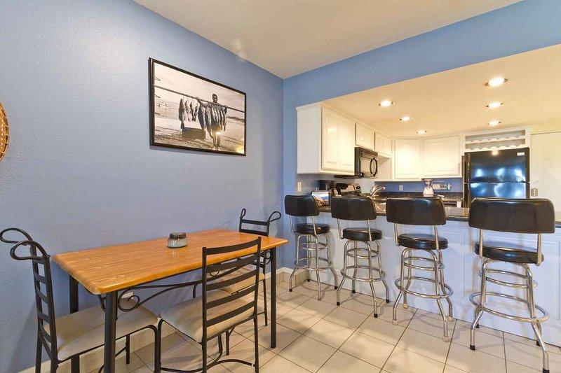 Mesa de comedor y asientos adicionales en el bar de la cocina.