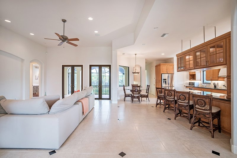 It does not get any better in this beautifully designed home.  A large sectional in the living area with a breakfast table and barstools.