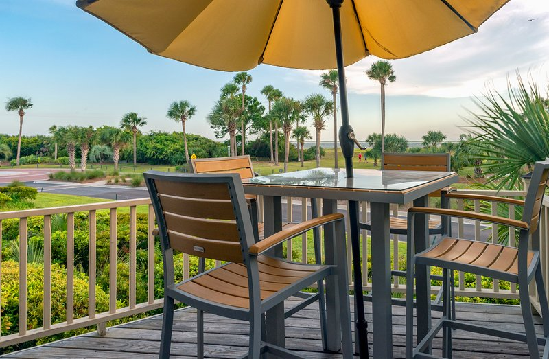 The deck overlooks the ocean, beach, and Deveaux Banks across the waters.