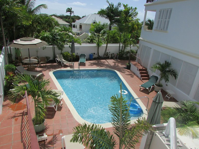 Private swimming pool with loungers, table and shaded area.